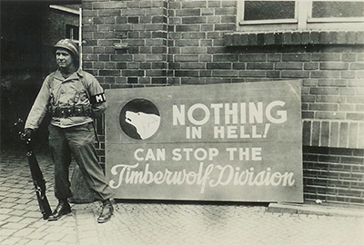 """A sign proudly displaying the 104th motto: """"Nothing in hell can stop the Timberwolf Division""""(Photo: unknown photographer)"""