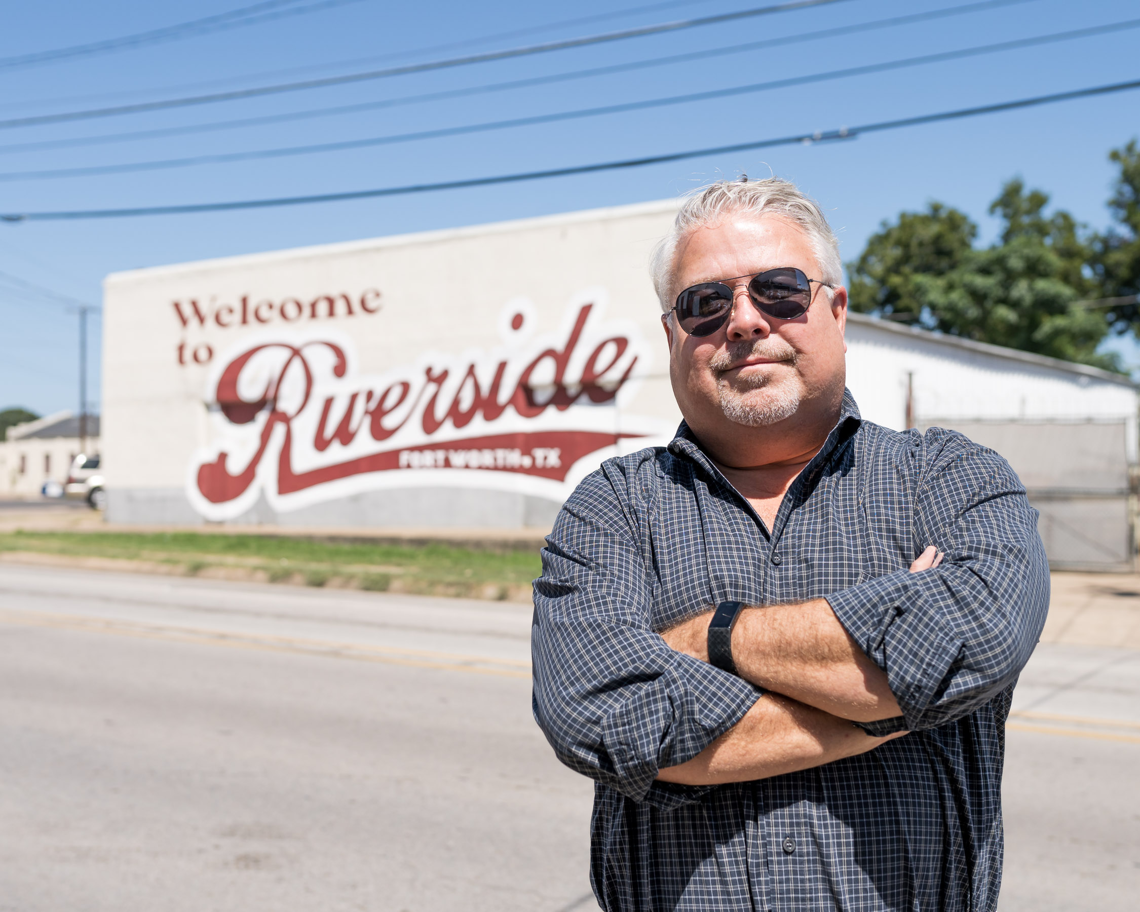 """Man wearing shades and crossing arms stands in front of a mural reading: """"Welcome to Riverside."""""""
