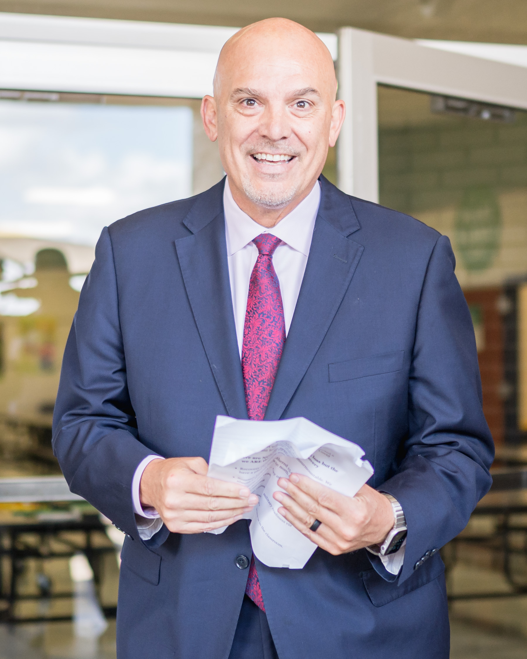 man in suit smiles and holds papers