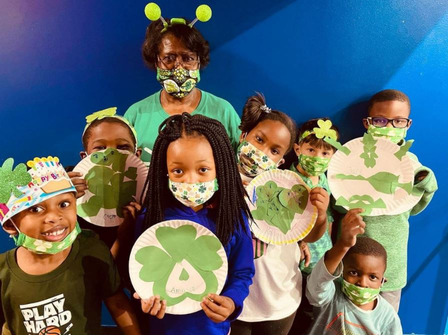 Family YMCA of Greater Augusta kids wearing green outfits and showing Shamrocks
