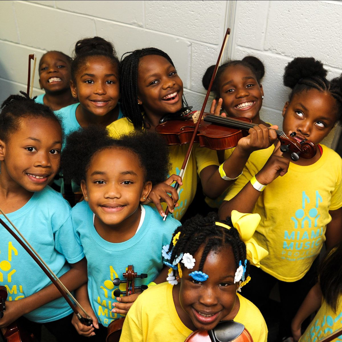 Smiling kids with string instruments.