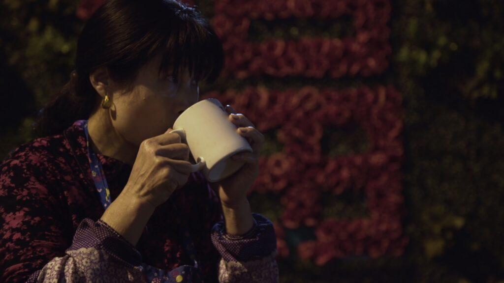 Capture du film présentant Ayi, la protagoniste du film, buvant dans une tasse en céramique blanche.