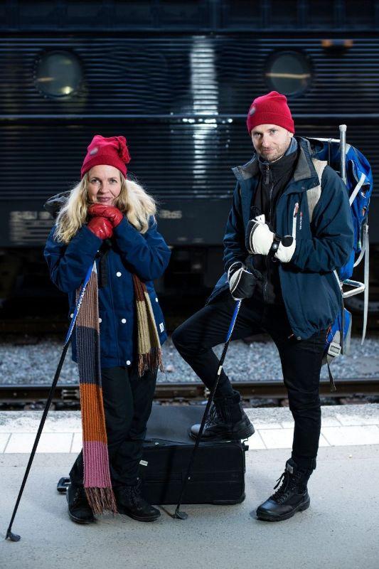 Susanna Elfors och Andreas Sidkvist står med vinterkläder och röda mössor på en perrong