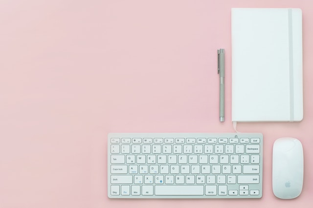 A pink tabletop with a keyboard, mouse, pen, and notebook