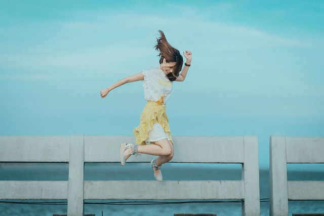 A woman jumping up in the air with joy
