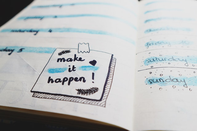 the words make it happen doodled in a notebook