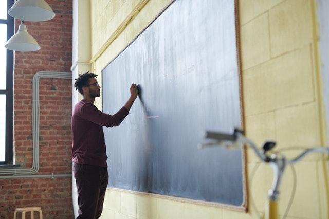 A man writing on a chalk board