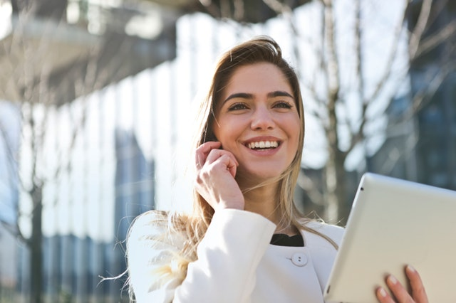 A woman smiling while holding a tablet