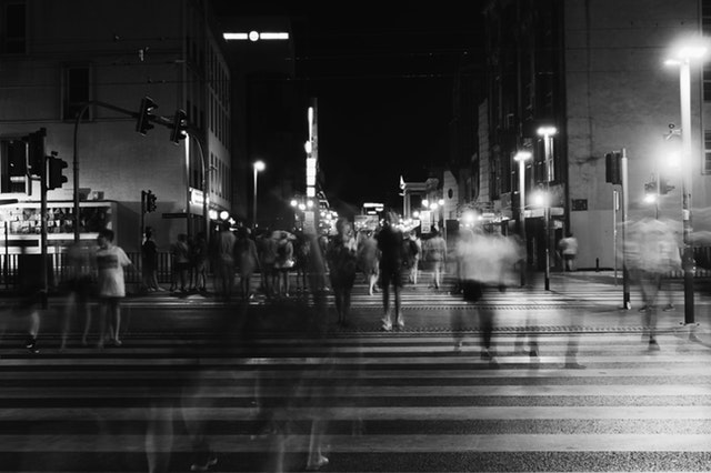 A black and white photo of a busy street at night