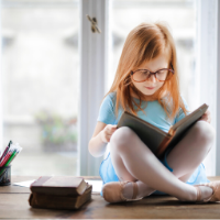 photo of girl with glasses reading a book
