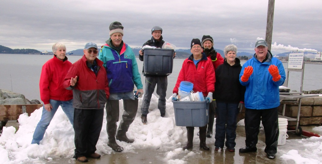 Group of volunteers standing in the snow with their supplies to do forage fish spawn sampling on the beach in early 2020.