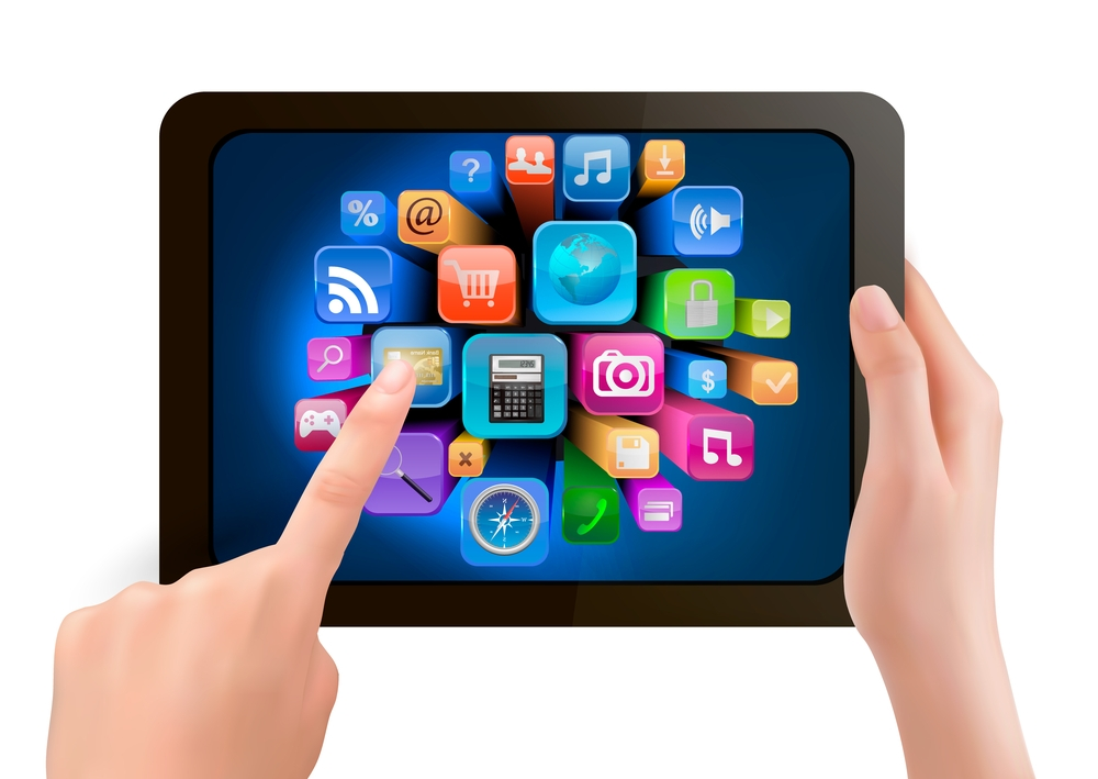Hands holding tablet with one finger touching icon on screen