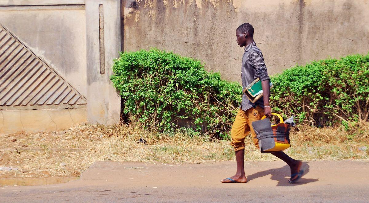 A Nigerian roadside shoemaker walking the streets in sandals