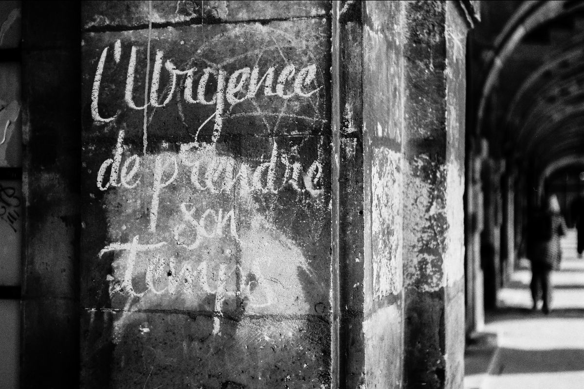 """A photograph of a chalkboard with French writing that says, """"The urgency of taking your time"""""""