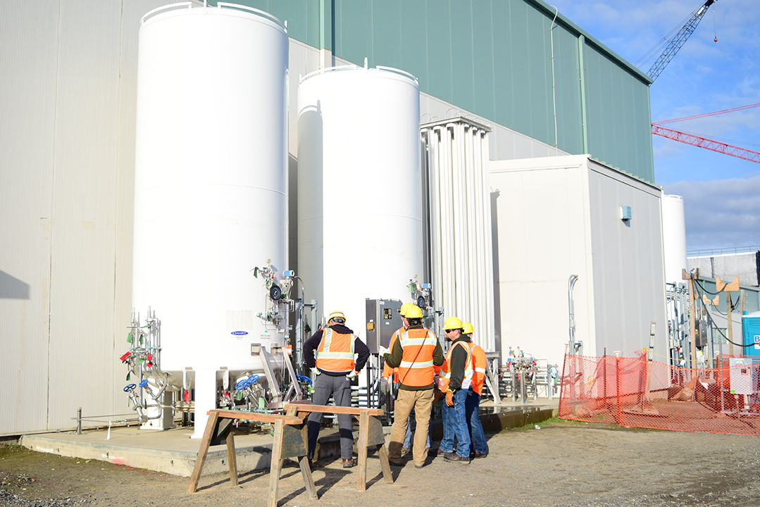 Workers inspect the gas storage distribution system tanks at the Analytical Laboratory.