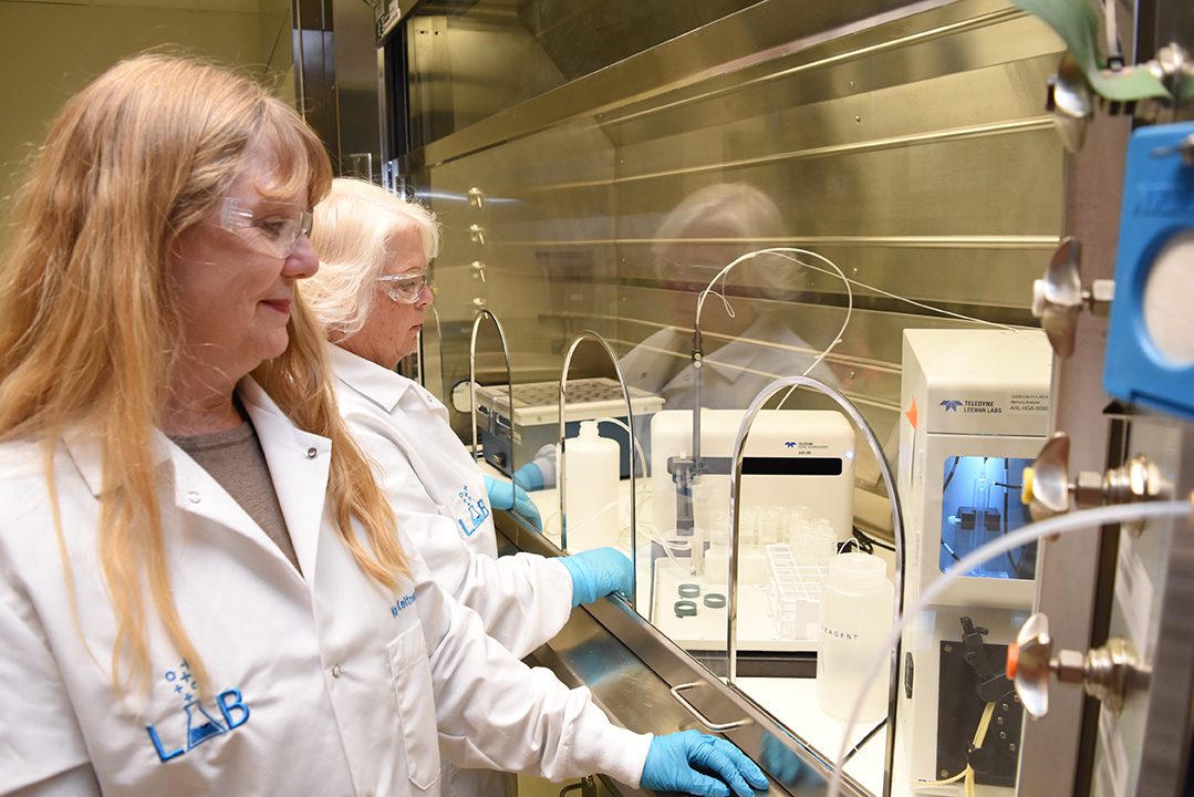 Vit Plant chemists work with scientific instruments inside the Analytical Laboratory.