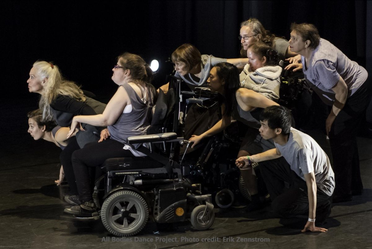 Photo of nine dancers huddled together, crouched and seated, attentively staring to the left.