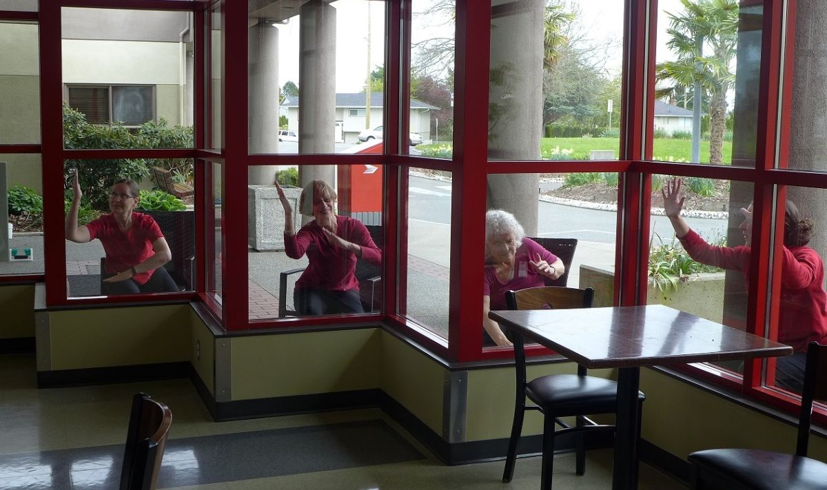 Four dancers are seated outside a wall of windows with their elbows bent at different angles. They wear red tops and are each framed by a square red window frame.