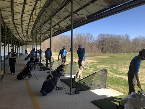 School golf team practicing golf on the driving range