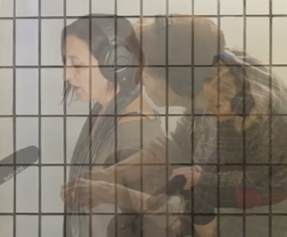 Screenshot from video. White mosaic background like a toilet's shower wall. Three images of white-skinned people are edited onto each other, each at about 40% opacity against the white mosaic and each other. People are speaking into a microphone and are wearing headphones. Two of these people are sitting down and the one most to the left is standing.