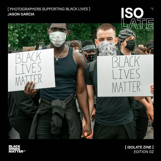Screenshot of ISOLATE ZINE cover. Square image shows in the middle on black cover. Two men hold hands and carry BLACK LIVES MATTER banners whilst holding hands and attending a protest. Man on the left is dark skinned and man on the right is light-skinned and both wear black clothing. Both men and other people behind them wear masks.