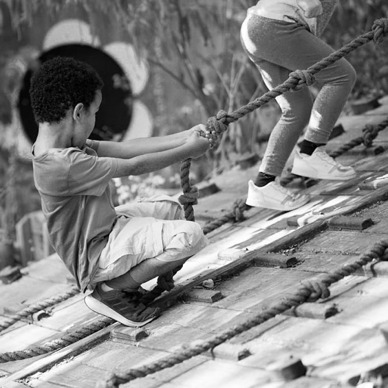 Black and white photograph. Two children hold on to rope whilst climbing up a wooden ramp in a children's playground outdoors.