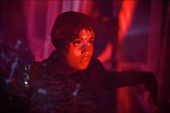 Photo of a live performance. A dark skinned person wearing dark clothes and looking away from the camera is illuminated in red stage light. The background is also illuminated red.
