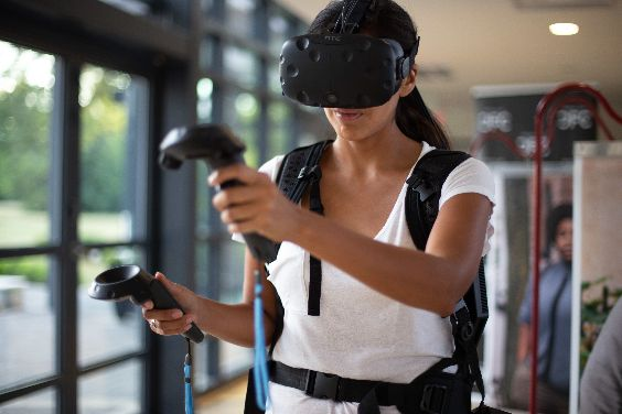 Photograph of dark skinned person wearing a VR head and hand set and moving their arms. Room is brightly lit.