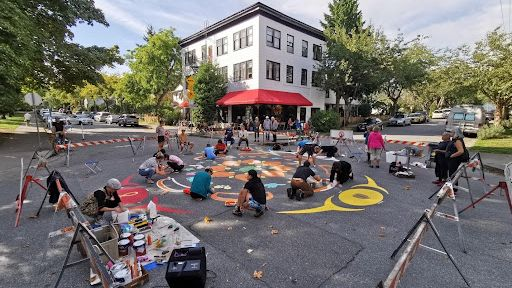 People painting a multi-coloured mural on the road intersection of hawks and keefer