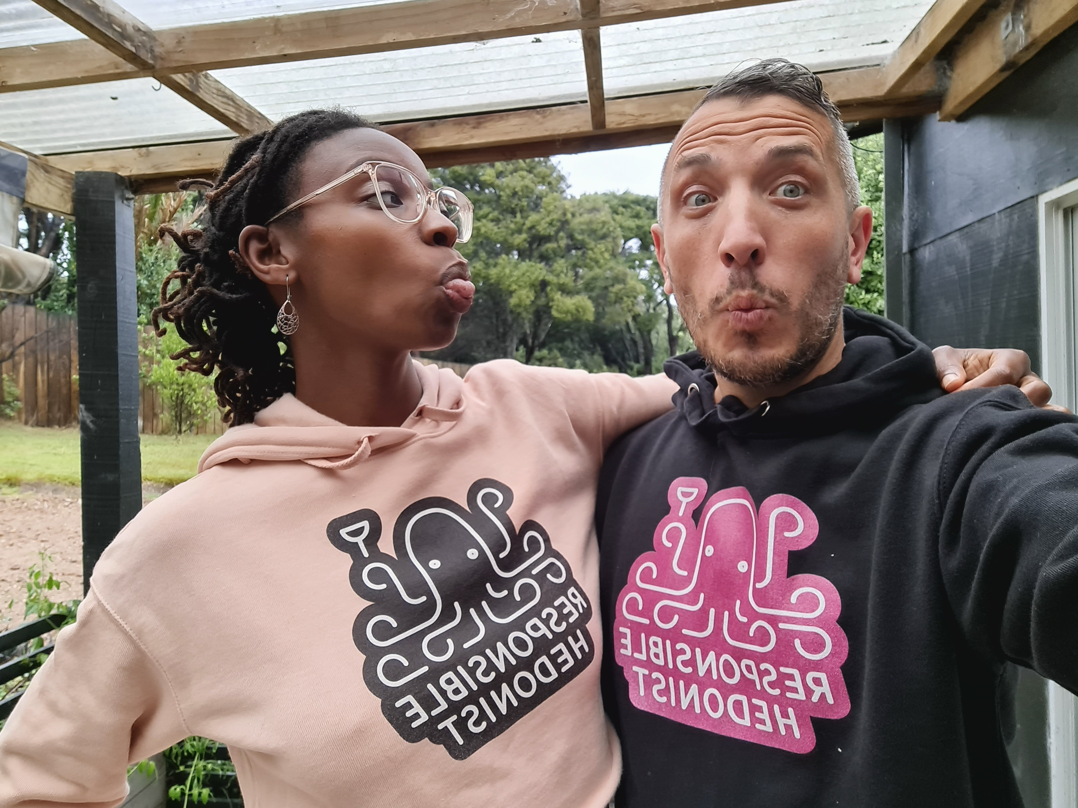 Diana and Frank in Responsible Hedonist hoodies with their tongues out playfully