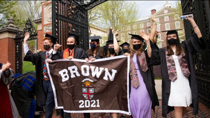 Group of 2021 graduates walking through the gates with a Brown banner