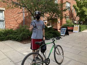 Student holding U-Lock next to a bicycle.