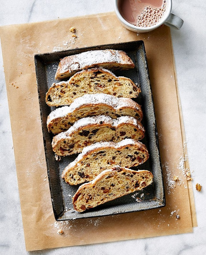 Slices of stollen laying in a pan, with a cup of warm cocoa next to it
