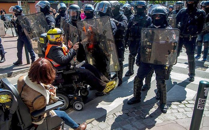 Odile Maurin and another woman in wheelchair facing the police during protest