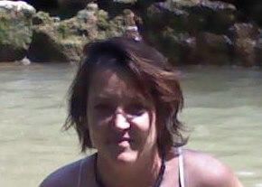 Portrait of Nathalie Dale, in front of the sea, mid long dark hair, dark eyes, smiling