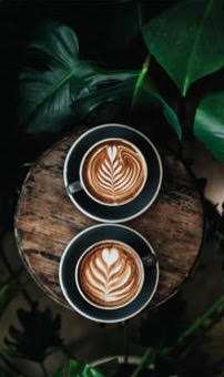 2 Coffees on round wooden board next to plant