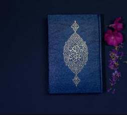 Blue Quran on blue background with pink flowers