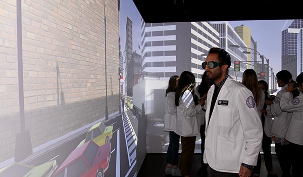 An optometry student in the virtual reality room wearing goggles and looking at a street scene.