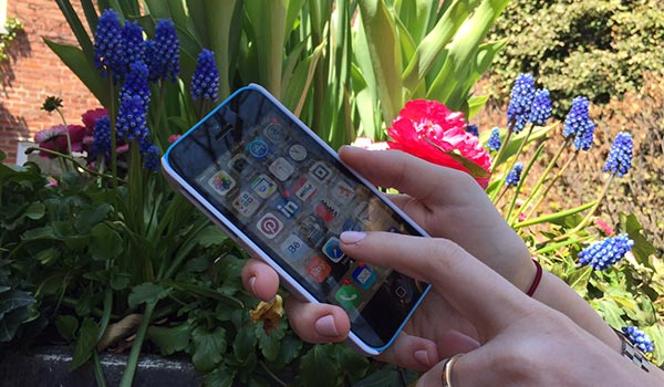 A hand holding an iPhone, pointing at the screen. Bright greenery appears behind the phone.