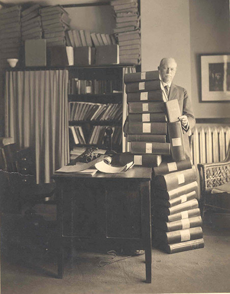 Black and white photo of William Hadley in his office next to a tall stack of books.
