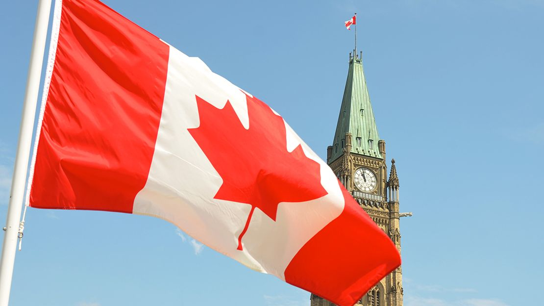 Canadian flag flying in breeze in foreground, background is the Canadian Peace Tower (Parliament Hill)