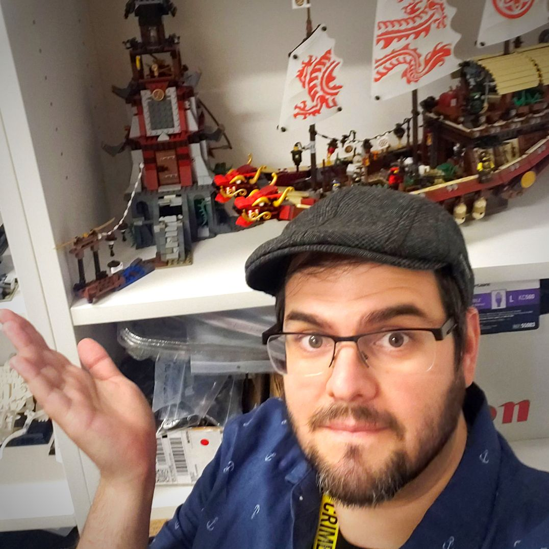 Man wearing hat and black rimmed glasses standing in front of a bookcase that features a lego pirate ship