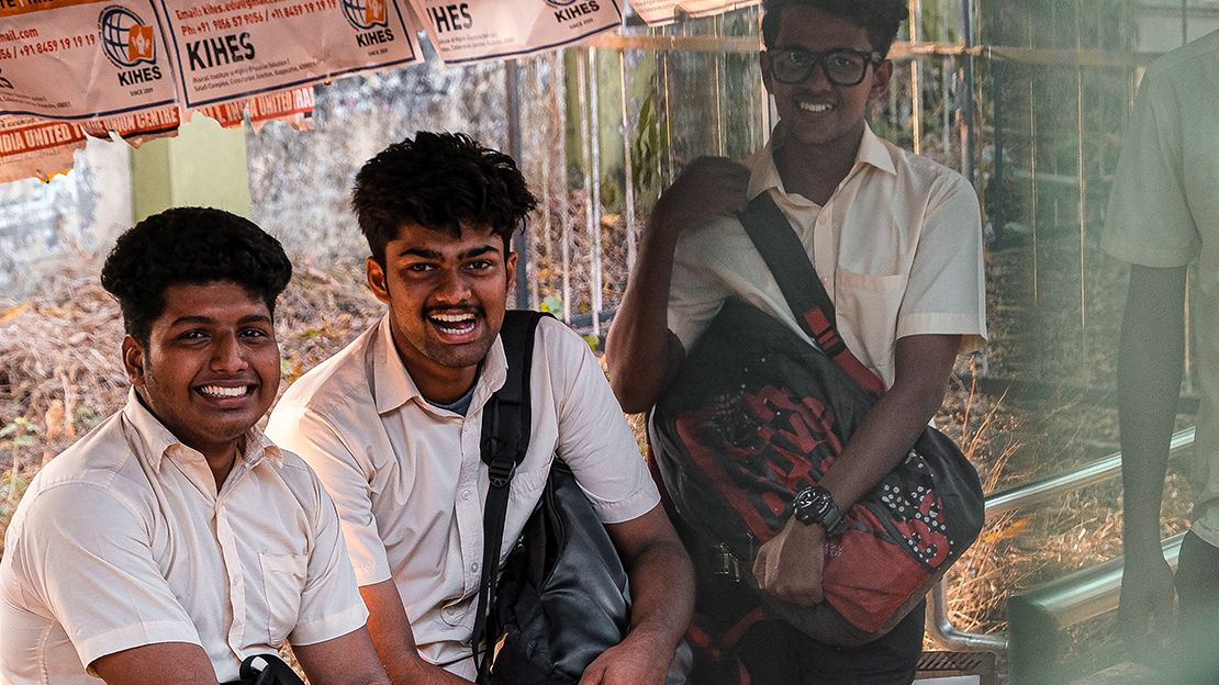 Three students wearing white button-down shirts and holding backpacks looking at the camera smiling while resting in covered walkway