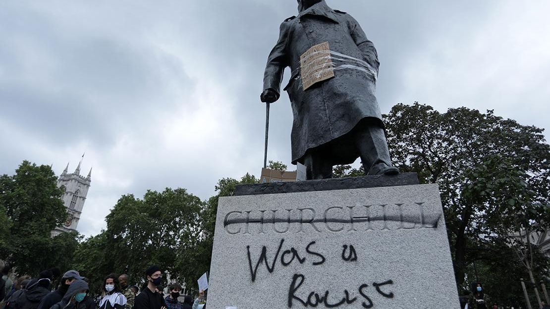 Statue of Winston Churchill with Churchill was a racist spray painted on concrete base of satue