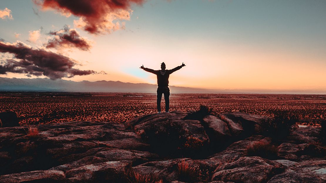 Person standing on reddish, rocky landscape, hands up in the air looking away from the camera toward a sunrise over mountains in the distance.