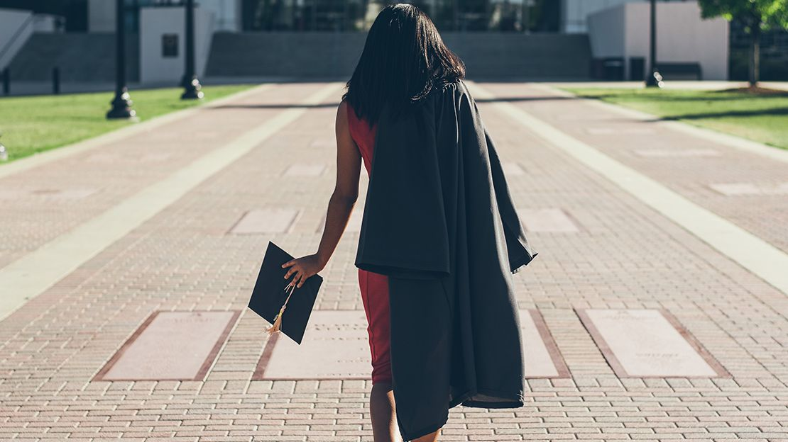 Woman walking away from camera toward building, wearing red dress, with grad robe thrown over her shoulder and a grad cap in her left hand