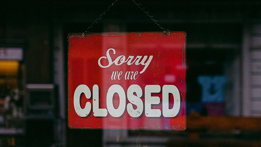 Red sign hanging in window that reads: Sorry, we are closed