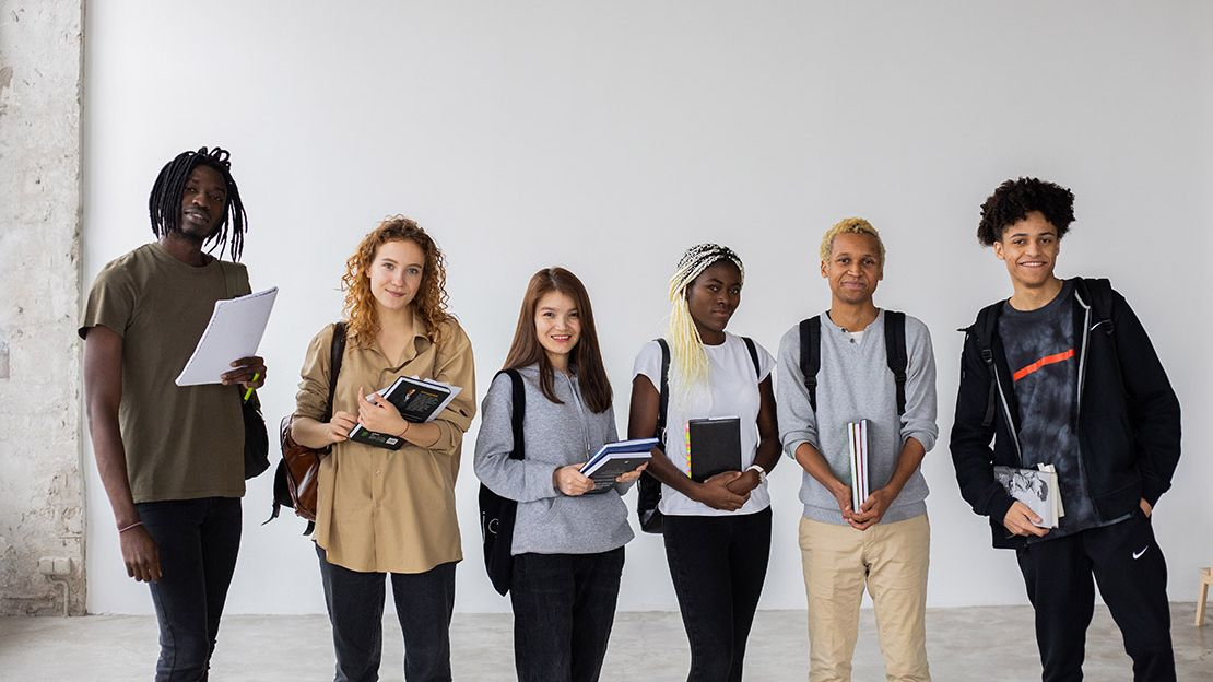 Six students lined up in front of blank wall, holding notebooks.