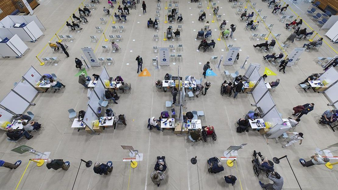 Overhead view of vaccine clinic. Rows of chairs with people sitting on them, at bottom of photo are two rows of 14 tables where people are sitting to receive a vaccine