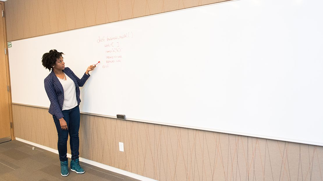 Woman wearing white t-shirt, blue pants and a blue blazer standing in front of a white board pointing to illegible writing